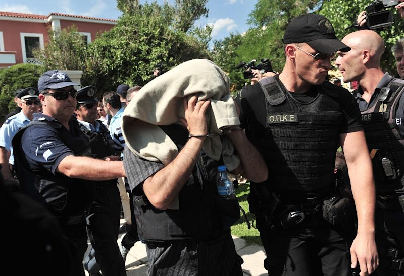 A Greek police officer escorts a Turkish officer who fled to Greece after the failed coup in Turkey, as he leaves a courthouse on July 21, 2016
