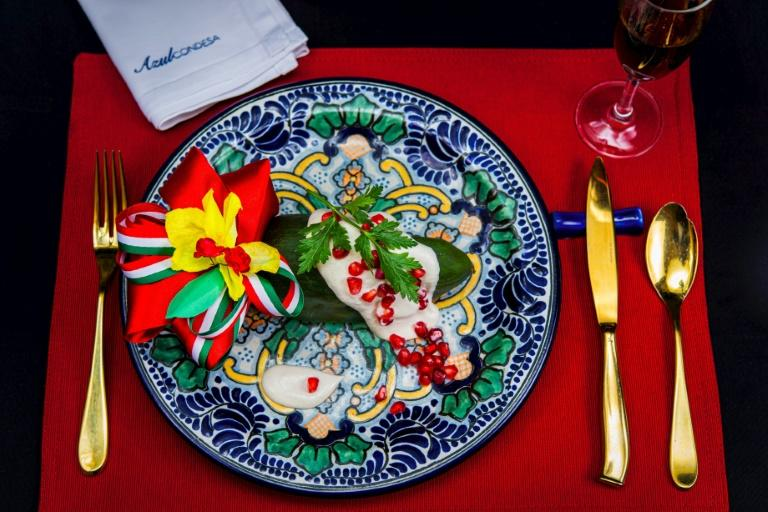 Chile en Nogada, an iconic Mexican dish featuring poblano chile peppers bathed in creamy white sauce and topped with red pomegranate seeds, from the Azul Condesa restaurant in Mexico City