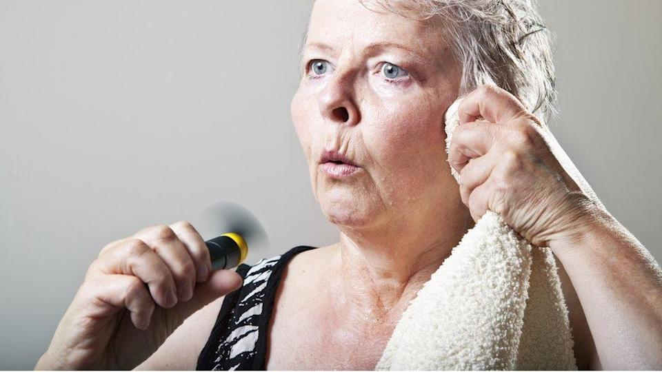 A woman going through a hot flush - she's holding a fan in one hand, while she wipes her face with a towel with the other hand