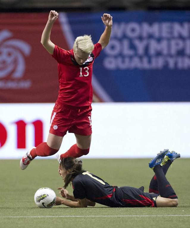 VANCOUVER, CANADA - JANUARY 27: Sophie Schmidt #13 of Canada jumps over a sliding Jenifer Ruiz #13 of Mexico during the first half of semifinals action of the 2012 CONCACAF Women's Olympic Qualifying Tournament at BC Place on January 27, 2012 in Vancouver, British Columbia, Canada. (Photo by Rich Lam/Getty Images)