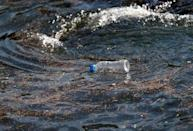 FILE PHOTO: A plastic bottle drifts on the waves of the sea at a fishing port in Isumi