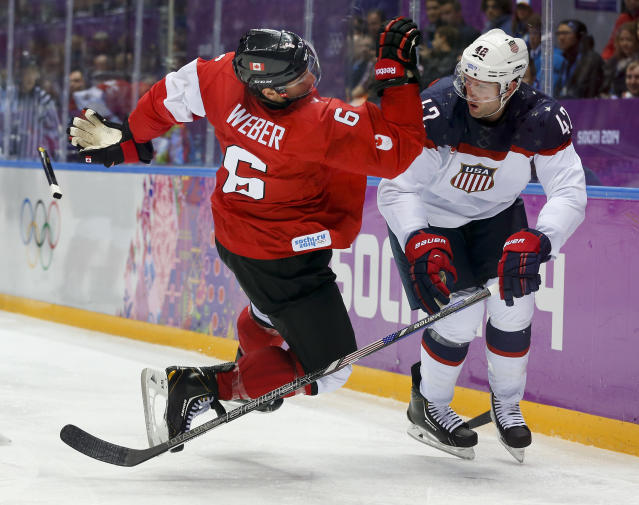 Canada defenseman Shea Weber, left, trips over USA forward David Backes during the third period of a men's semifinal ice hockey game at the 2014 Winter Olympics, Friday, Feb. 21, 2014, in Sochi, Russia. (AP Photo/Julio Cortez)