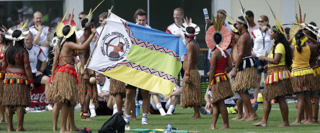 German's national soccer player Miroslav Klose dances with Brazilian indigenous after a training near Porto Seguro, Brazil, Monday, June 9, 2014. Germany will play in group G of the 2014 soccer World Cup. (AP Photo/Matthias Schrader)