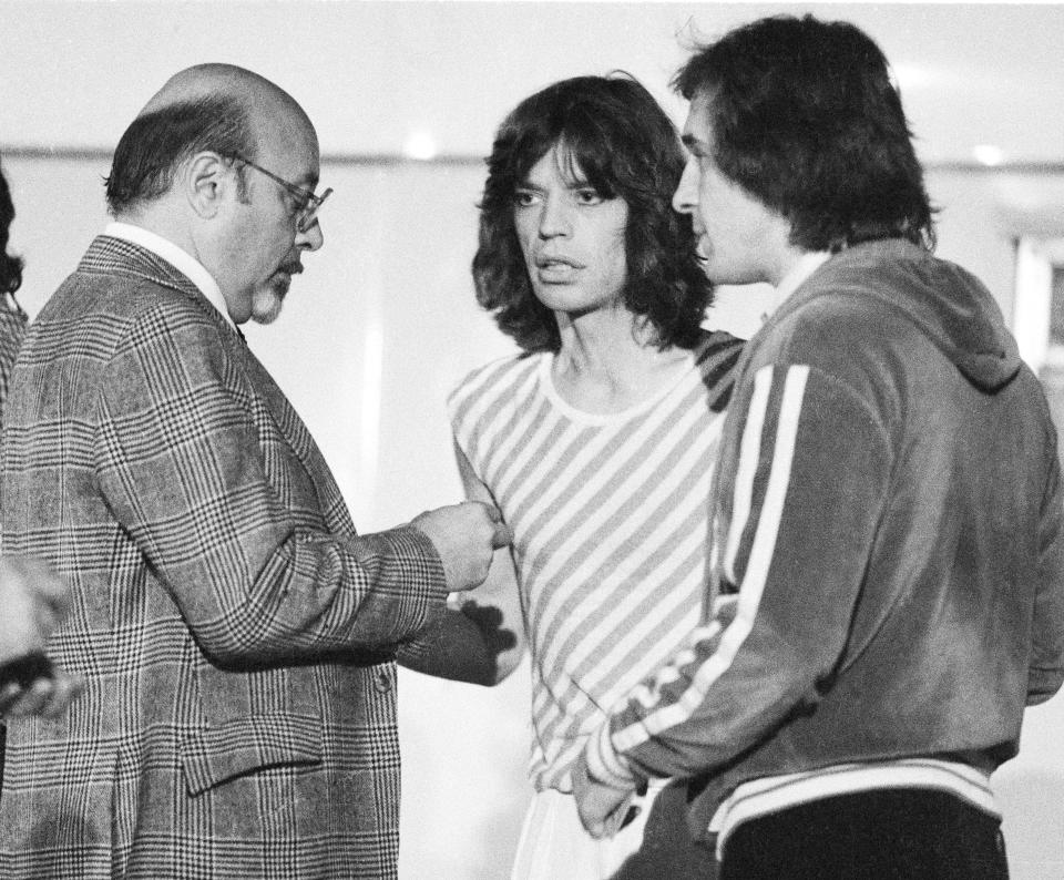 Ahmet Ertegun, head of Atlantic Records, talks to Mick Jagger and Peter Rudge, backstage at a Rolling Stones concert at Earls Court, London, May 1976. (Photo by Michael Putland/Getty Images)