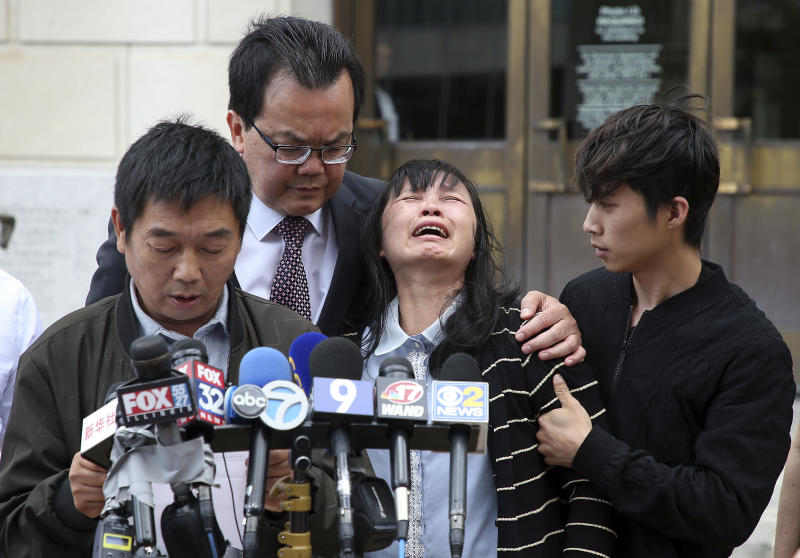 Lifeng Ye, the mother of slain University of Illinois scholar Yingying Zhang, cries out in grief as her husband Ronggao Zhang, far left, addresses the media after a jury found Brendt Christensen guilty of her murder Monday, June 24, 2019 outside the U.S. Federal Courthouse in Peoria, Ill. Consoling her is her son Zhengyang Zhang, far right, and family friend Dr. Kim Tee. (Terrence Antonio James/Chicago Tribune via AP)
