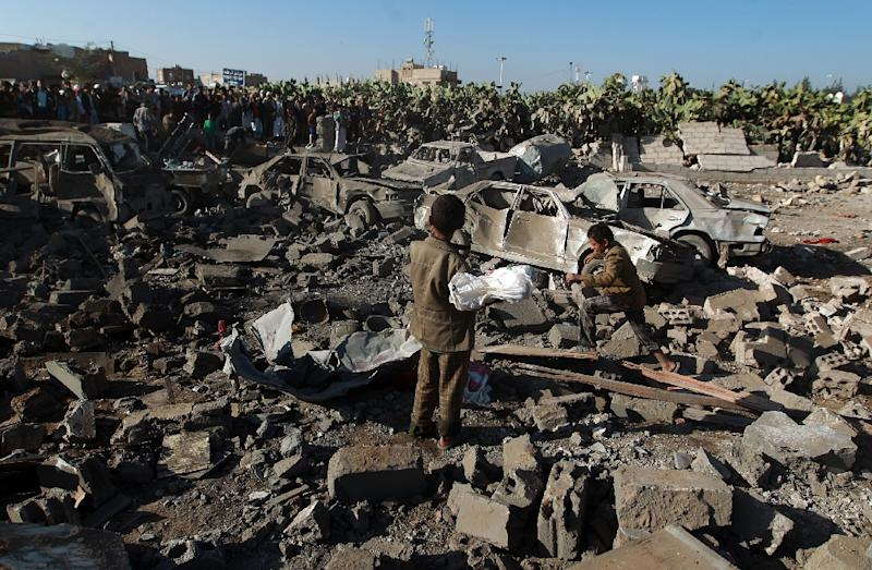Yemenis stand at the site of a Saudi air strike against Huthi rebels near Sanaa Airport on March 26, 2015 (AFP Photo/Mohammed Huwais)