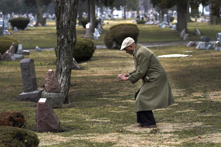 """Tony Burroughs, CEO of Chicago's Center for Black Genealogy, bends down Wednesday, March 17, 2021, to take a photo at the gravesite of his great-grandparents in the Oakridge Cemetery in Hillside, Ill. """"I realized they were right under my feet,"""" he said. """"I can resurrect my ancestors that are not in history books but they live. They survive….And it's up to me to tell their stories."""" (AP Photo/Charles Rex Arbogast)"""