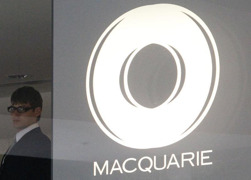 A security worker stands next to the Macquarie Group logo in central Sydney
