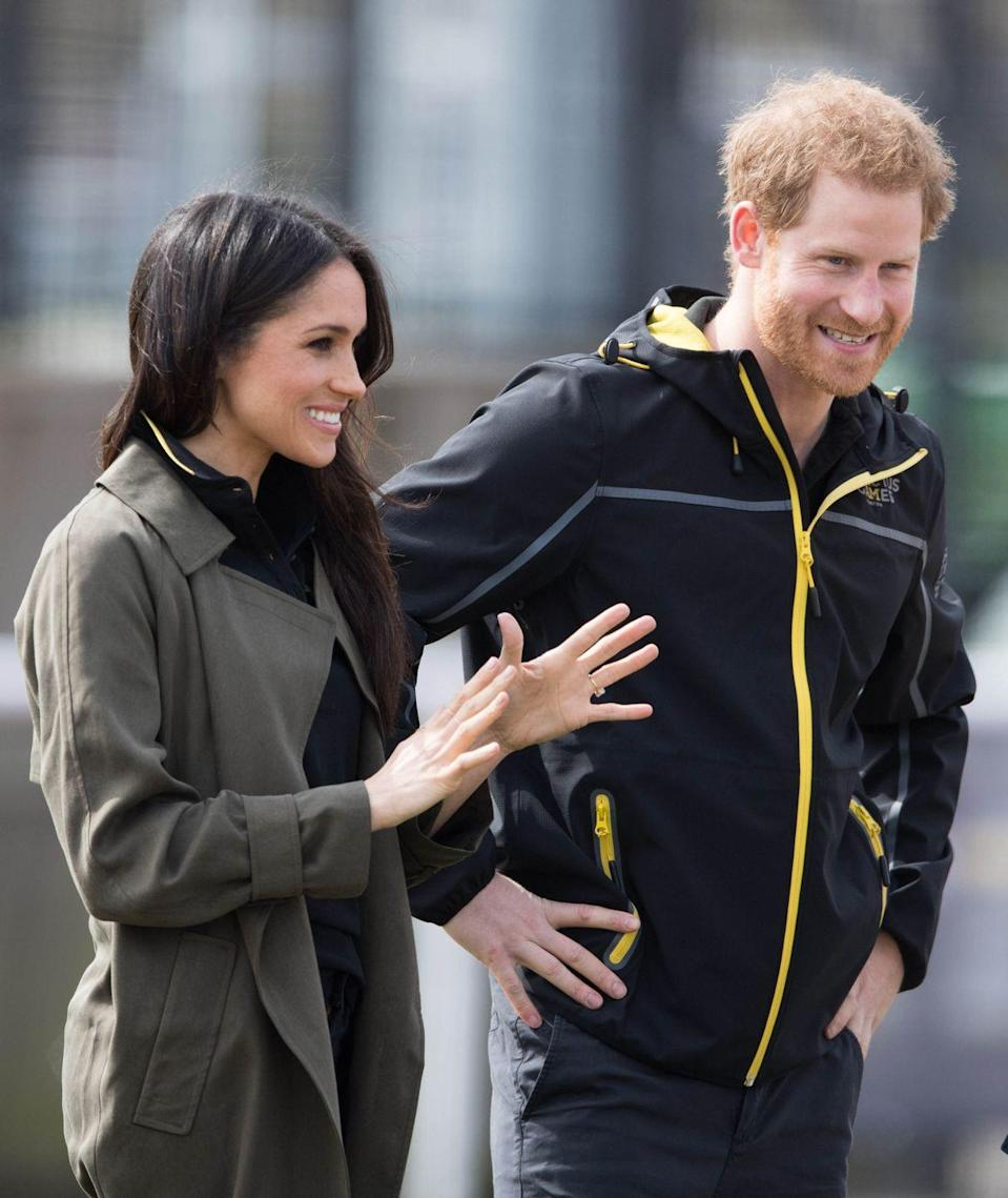 "<p>Appearing at the <a href=""https://www.harpersbazaar.com/celebrity/latest/a19703513/meghan-markle-prince-harry-invictus-games-sydney/"" rel=""nofollow noopener"" target=""_blank"" data-ylk=""slk:UK Team Trials for the Invictus Games"" class=""link rapid-noclick-resp"">UK Team Trials for the Invictus Games</a>, the future Duchess went sporty chic in an <a class=""link rapid-noclick-resp"" href=""https://www.aritzia.com/us/en/product/lawson-trench-coat/50438025.html?country=us"" rel=""nofollow noopener"" target=""_blank"" data-ylk=""slk:army green trench coat"">army green trench coat</a> by Babaton for <a href=""https://www.harpersbazaar.com/fashion/trends/a19718329/meghan-markle-aritzia/"" rel=""nofollow noopener"" target=""_blank"" data-ylk=""slk:Aritzia"" class=""link rapid-noclick-resp"">Aritzia</a>, smiling beside her husband-to-be.</p>"