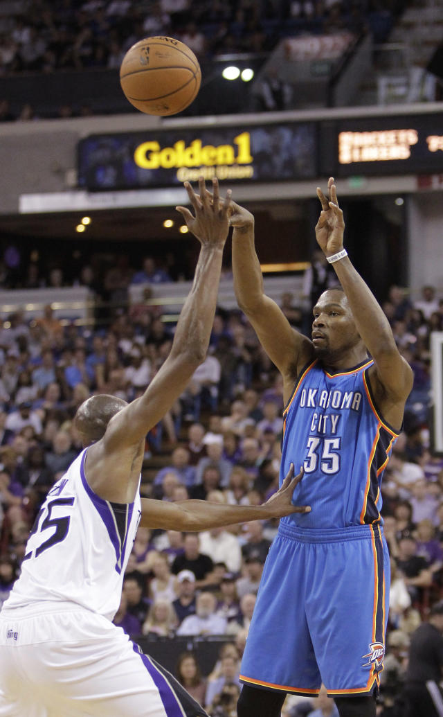 Oklahoma City Thunder forward Kevin Durant, right, passes over Sacramento Kings forward Travis Outlaw during the first quarter of an NBA basketball game, Tuesday, April 8, 2014, in Sacramento, Calif. (AP Photo/Rich Pedroncelli)