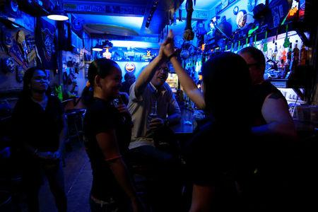 American James John Goodman, 51, does a high-five with female servers inside a bar in Subic, north of Manila, Philippines November 10, 2017. Picture taken November 10, 2017. REUTERS/Romeo Ranoco