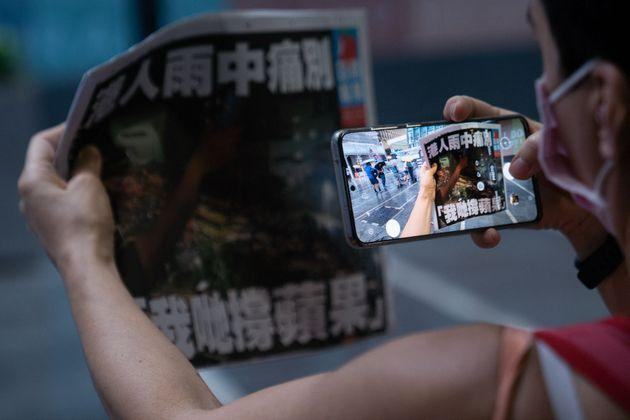 A woman takes a photo of the Apple Daily newspaper's final edition in Hong Kong's Central district on June 24, 2021, after the pro-democracy tabloid was forced to close after 26 years under a sweeping new national security law. (Photo by Bertha WANG / AFP) (Photo by BERTHA WANG/AFP via Getty Images) (Photo: BERTHA WANG via Getty Images)
