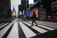 FILE - In this March 23, 2020, file photo, a man crosses the street in a nearly empty Times Square, which is usually very crowded on a weekday morning in New York. (AP Photo/Mark Lennihan, File)