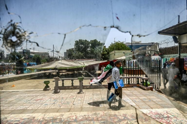A Sudanese protester walks near building outside the army headquarters in the capital Khartoum on Monday