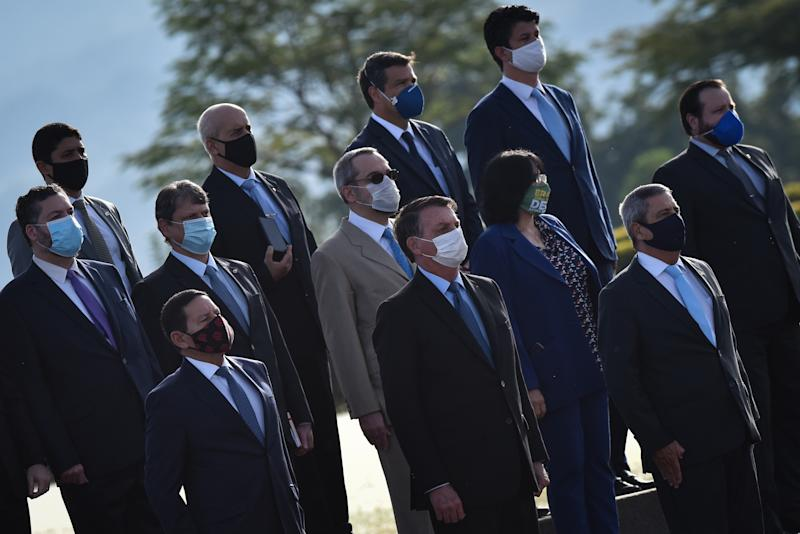 Wearing a protective face mask, Brazil's president Jair Bolsonaro and other Brazil's ministers attend the National Flag Raising ceremony in front of Alvorada Palace amid the Coronavirus (COVID-19) pandemic, in Brasilia, Brazil, on Tuesday, June 9, 2020. (Photo by Andre Borges/NurPhoto via Getty Images)