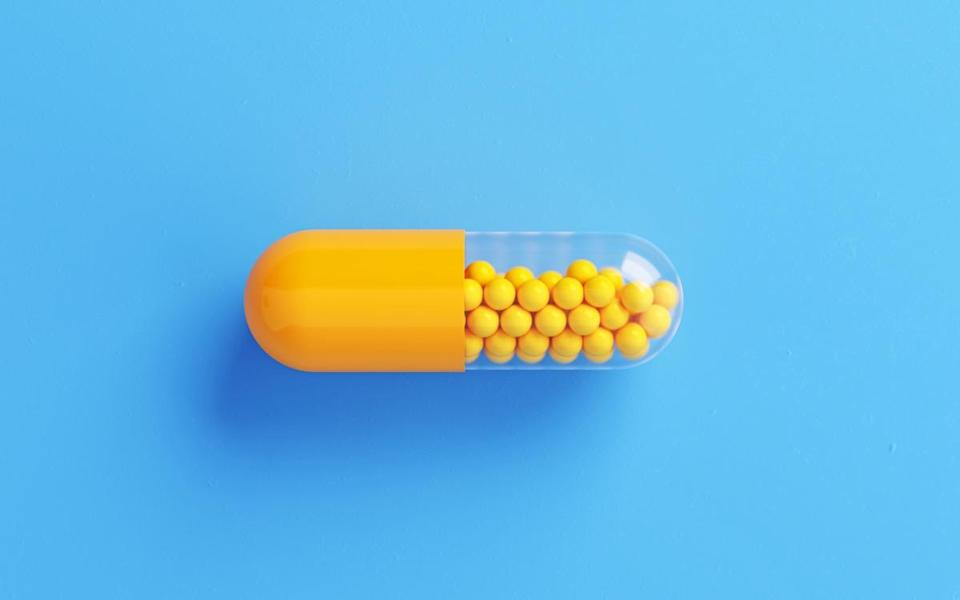 Yellow Pill bottle on Blue Background.