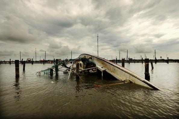 A boat overturned by Hurricane Isaac floats in lower Plaquemines Parish on September 2, 2012 in Buras, Louisiana. Today was the first day some residents of lower Plaquemines were allowed to return to assess damage to their homes. (Photo by Mario Tama/Getty Images)