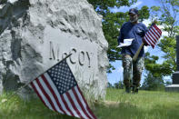 Bob Workman of Boston, a retired Marine Gunnery Sgt., and past commander of the Boston Police VFW, searches for veteran's graves to make sure flags are placed at each one ahead of Memorial Day, Thursday, May 27, 2021, in the Fairview Cemetery in Boston. After more than a year of isolation, military veterans say wreath-laying ceremonies, barbecues at local vets halls and other familiar traditions are a welcome chance for them to reconnect with fellow service members and renew solemn traditions honoring the nation's war dead. (AP Photo/Josh Reynolds)