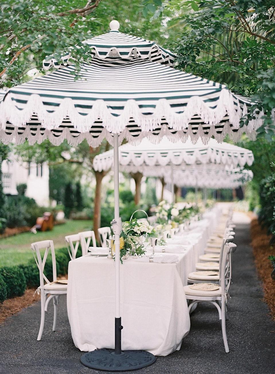 """The umbrellas!! We did one long table and spaced everyone out. We used all of our family silver, which I love. So someone had a baby cup with flowers in front of them and a goblet with my cousin's initials. We were even able to find an old napkin ring for Walker's dad—a napkin ring that was engraved """"Dad""""!"""