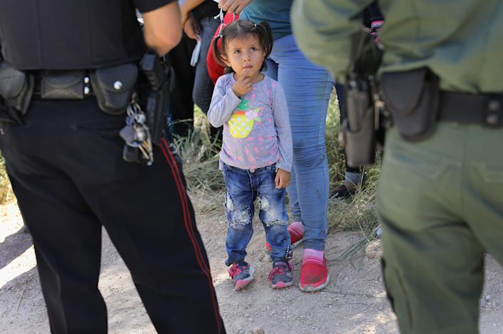 A Mission Police Dept. officer, left, and a U.S. Border Patrol agent watch over a group of Central American asylum seekers before taking them into custody on June 12, 2018, near McAllen, Texas.