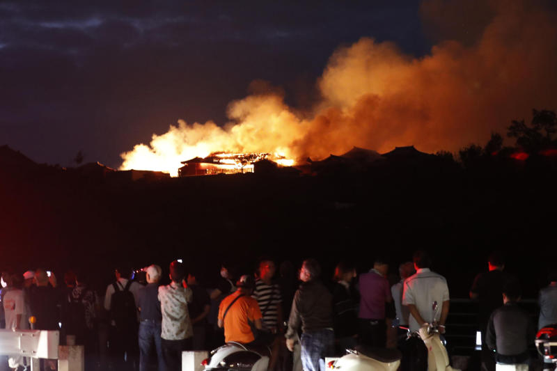People watch as smoke and flames rise from burning Shuri Castle in Naha, Okinawa, southern Japan, Thursday, Oct. 31, 2019. A fire broke out at the historic Shuri Castle on Japan's southern island of Okinawa, nearly destroying it. (Jun Hirata/Kyodo News via AP)