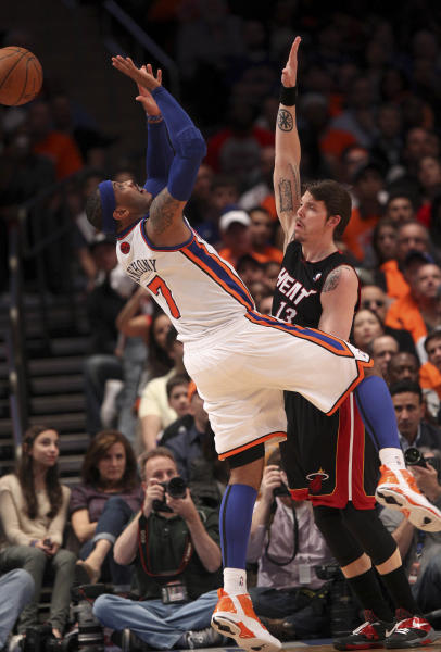 New York Knicks' Carmelo Anthony, left, is fouled by Miami Heat's Mike Miller in the first half of an NBA basketball game in New York, Sunday, April 15, 2012. (AP Photo/Seth Wenig)