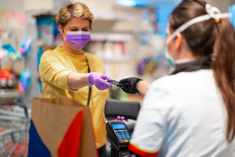 Cashier returning credit card at the cash register to woman with wallet wearing protective face mask and gloves to prevent viruses