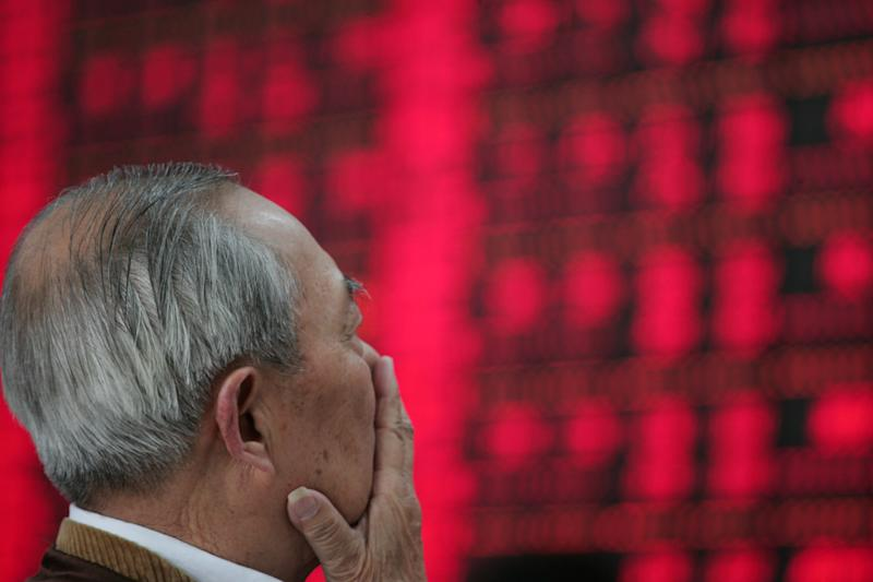 FILE- In this June 1, 2012, file photo, an investor looks at the stock price monitor at a private securities company in Shanghai, China. The global economy's foundations are weakening, one by one. Already hobbled by Europe's debt crisis, the world now risks being hurt by slowdowns in its economic powerhouses. (AP Photo)