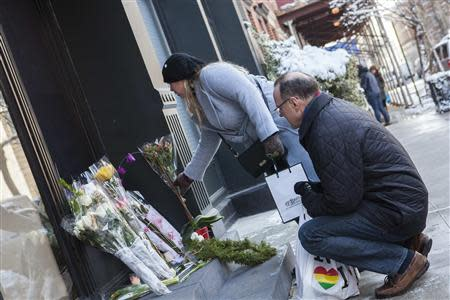 Passersby leave flowers on a makeshift memorial for actor Philip Seymour Hoffman in front of his apartment building in the Manhattan borough of New York, February 4, 2014. REUTERS/Keith Bedford