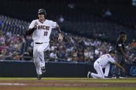 Arizona Diamondbacks' Carson Kelly runs to home plate to score a run against the San Francisco Giants as Diamondbacks third base coach Tony Perezchica (3) signals to a base runner and umpire Ramon De Jesus (18) looks on during the first inning of a baseball game, Thursday, Aug. 5, 2021, in Phoenix. (AP Photo/Ross D. Franklin)