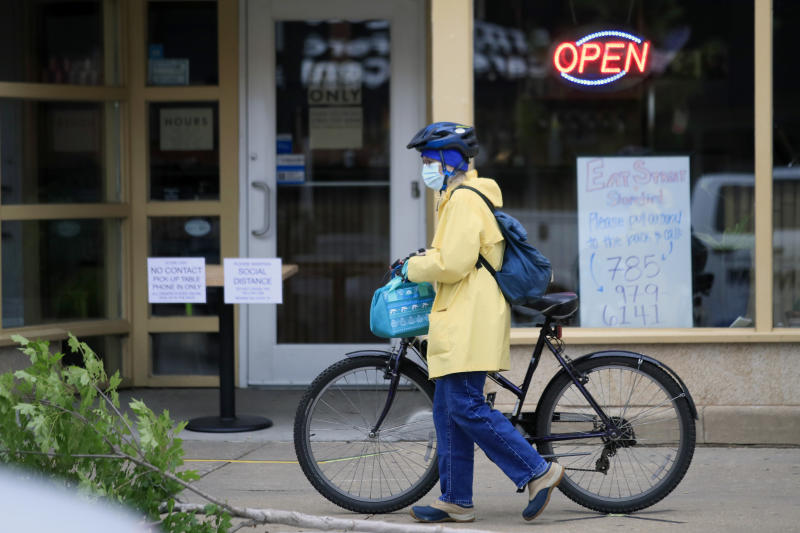 A customer arrives for a pickup dinner at a downtown restaurant In Lawrence, Kan., Monday, May 4, 2020. Restaurant dining rooms, retail stores and some offices began reopening Monday after Kansas lifted a statewide stay-at-home order, though some business owners hesitated, still concerned about the novel coronavirus. (AP Photo/Orlin Wagner)