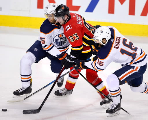 Calgary Flames' Sam Bennett (93) is sandwiched between Edmonton Oilers' Darnell Nurse (25) and Jujhar Khaira during first period NHL hockey action in Calgary, Alberta, Saturday, March 31, 2018. (Larry MacDougal/The Canadian Press via AP)