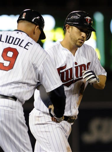 Minnesota Twins third base coach Steve Liddle congratulates Trevor Plouffe on his game-tying home run off Kansas City pitcher Greg Holland in the ninth inning of a baseball game, Thursday, Sept. 13, 2012, in Minneapolis. (AP Photo/Jim Mone)