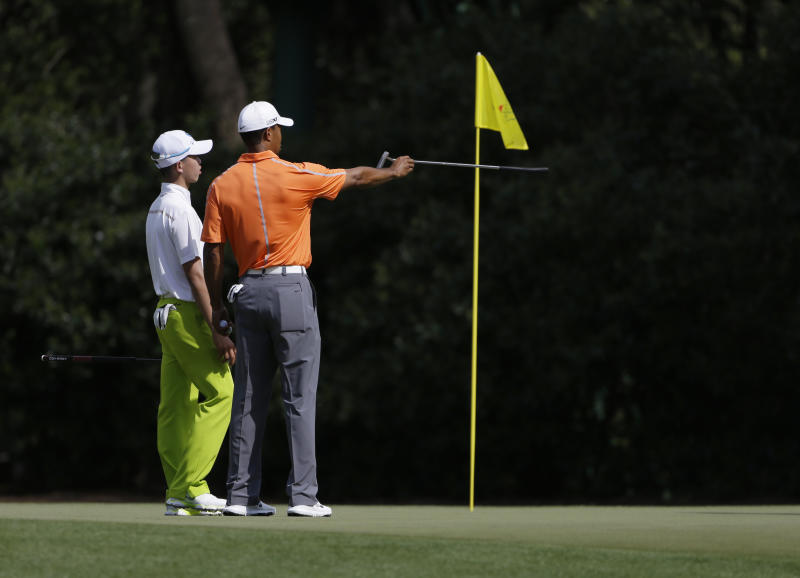 Tiger Woods, right, gives direction to amateur Guan Tianlang, of China, on the 11th green during a practice round for the Masters golf tournament Monday, April 8, 2013, in Augusta, Ga. (AP Photo/Darron Cummings)