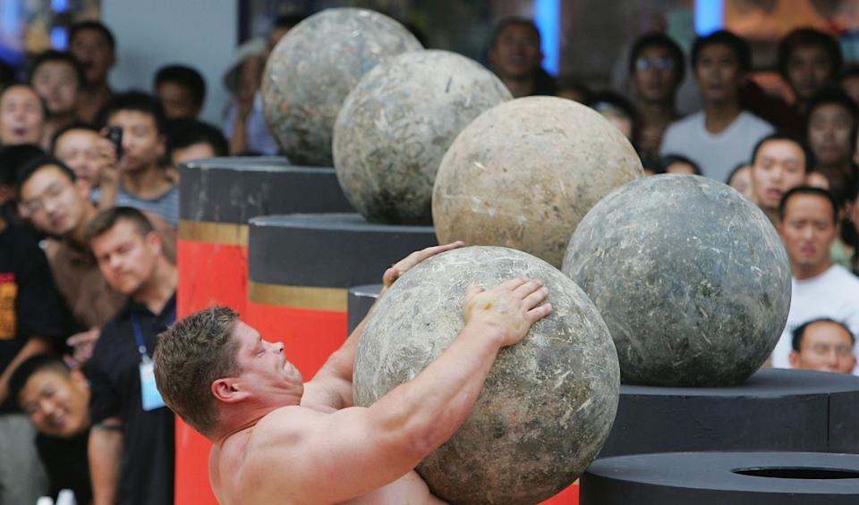 CHENGDU, CHINA - SEPTEMBER 30: (CHINA OUT) Mark Philippi of USA lifts an Atlas Stone during a match of the 2005 World's Strongest Man Competition at the Chunxi Road on September 30, 2005 in Chengdu of Sichuan Province, southwest China. Ten contestants are left for the next round of matches after elimination rounds of the competition which lasts from September 27 to October 7 in Chengdu. (Photo by China Photos/Getty Images)