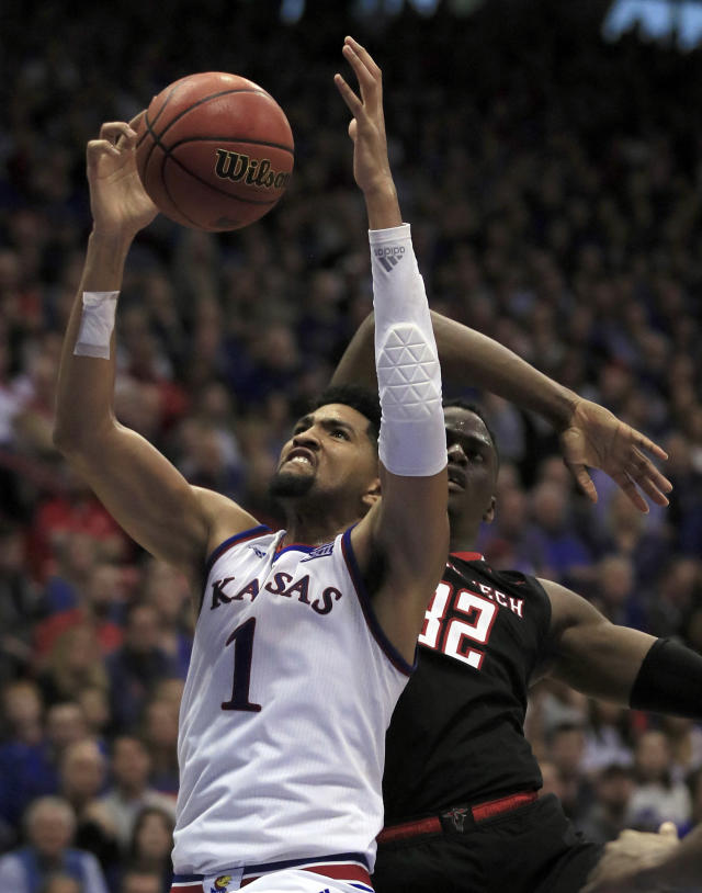Kansas forward Dedric Lawson (1) rebounds against Texas Tech center Norense Odiase (32) during the second half of an NCAA college basketball game in Lawrence, Kan., Saturday, Feb. 2, 2019. (AP Photo/Orlin Wagner)