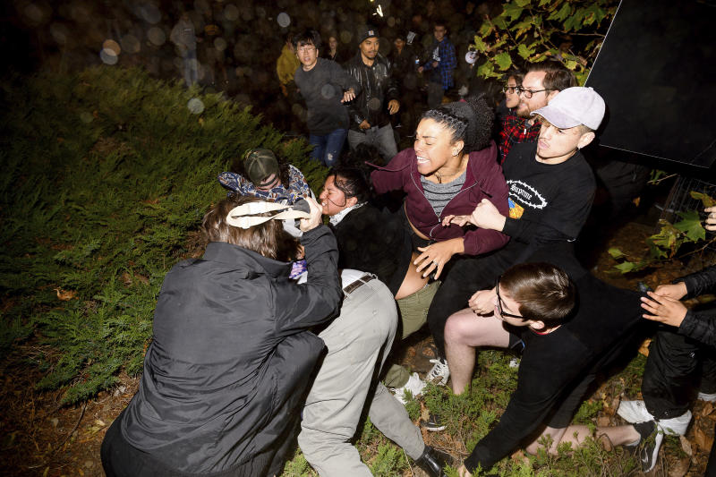 """A man pushed by protesters is surrounded as he falls to the ground while leaving a speech by conservative commentator Ann Coulter at the University of California, Berkeley, Wednesday, Nov. 20, 2019, in Berkeley, Calif. Hundreds of demonstrators gathered as Coulter delivered a speech titled """"Adios, America!"""" (AP Photo/Noah Berger)"""