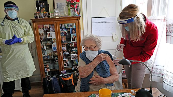 Jeannine Flamand receives her COVID-19 vaccine in the kitchen of her home in Warwick, R.I. (Suzanne Kreiter/The Boston Globe via Getty Images)