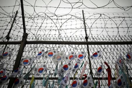 FILE PHOTO: South Korean national flags hang on a barbed-wire fence near the demilitarized zone separating the two Koreas in Paju, South Korea, August 14, 2017.  REUTERS/Kim Hong-Ji