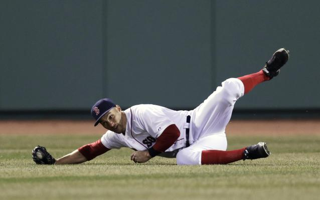 Boston Red Sox center fielder Grady Sizemore rolls as he makes the catch on a sacrifice fly by Texas Ranger Mitch Moreland, which scored Adrian Beltre, during the fourth inning of a MLB baseball game at Fenway Park, Monday, April 7, 2014, in Boston.(AP Photo/Charles Krupa)