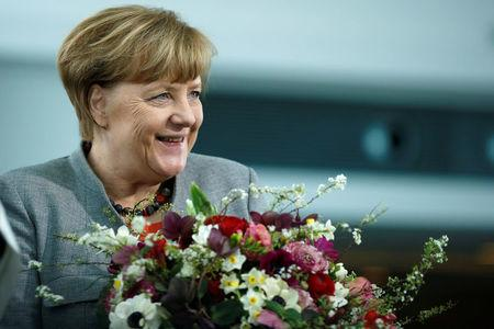 Chancellor Angela Merkel receives Valentine's Day flowers from the Central Gardening Association at the Chancellery in Berlin, Germany, February 9, 2018.    REUTERS/Axel Schmidt