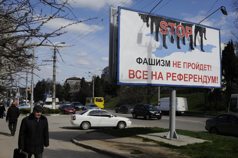 "People walk by a poster reading ""Fascism won't succeed. Everybody to the referendum!"" in Sevastopol, Thursday, March 13, 2014. Crimea plans to hold a referendum on upcoming Sunday that will ask residents if they want the territory to become part of Russia. Ukraine's government and Western nations have denounced the referendum as illegitimate and warned Russia against trying to annex Crimea. (AP Photo/Andrew Lubimov)"