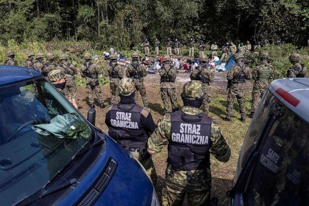 PHOTO: Polish border guards (foreground) stand next to migrants, believed to be from Afghanistan, in the village of Usnarz Gorny, Poland, near the border with Belarus, on Aug. 20, 2021. (Wojtek Radwanski/AFP via Getty Images)