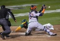 Oakland Athletics' Ramon Laureano scores as Houston Astros catcher Martin Maldonado (15) waits for the throw on a sacrifice fly hit by Mitch Moreland during the fourth inning of a baseball game Friday, April 2, 2021, in Oakland, Calif. (AP Photo/Tony Avelar)