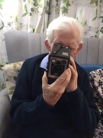 A care home resident using a camera from one of the memory boxes
