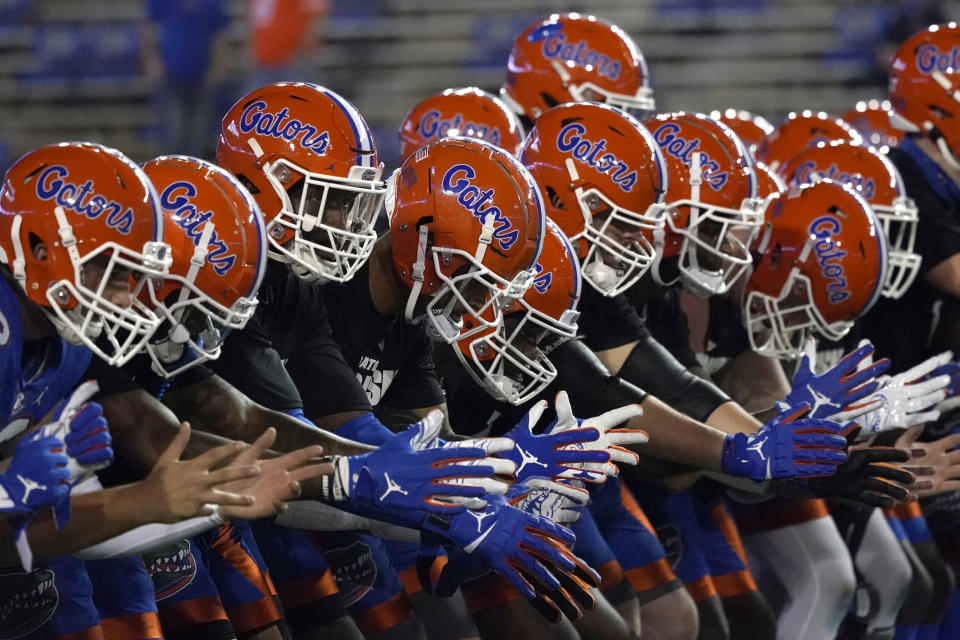 FILE - In this Dec. 12, 2020, file photo, Florida players get ready before an NCAA college football game in Gainesville, Fla. Florida's athletic department had a $54.5 million shortfall during the 2020-21 fiscal year because of the coronavirus pandemic, significant financial losses the Gators were able to weather with a supplement from the Southeastern Conference and a sizeable reserve. (AP Photo/John Raoux, File)