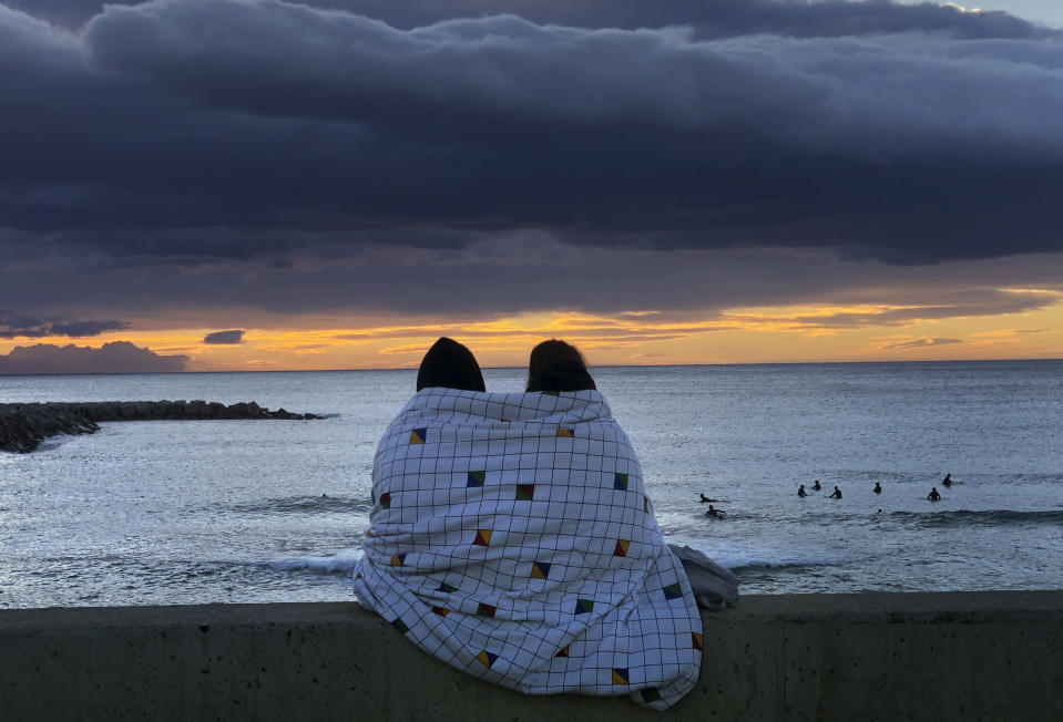 A couple share a blanket as they watch the sunrise in front of the Mediterranean Sea in Barcelona, Spain, Sunday, Jan. 24, 2021. (AP Photo/Emilio Morenatti)