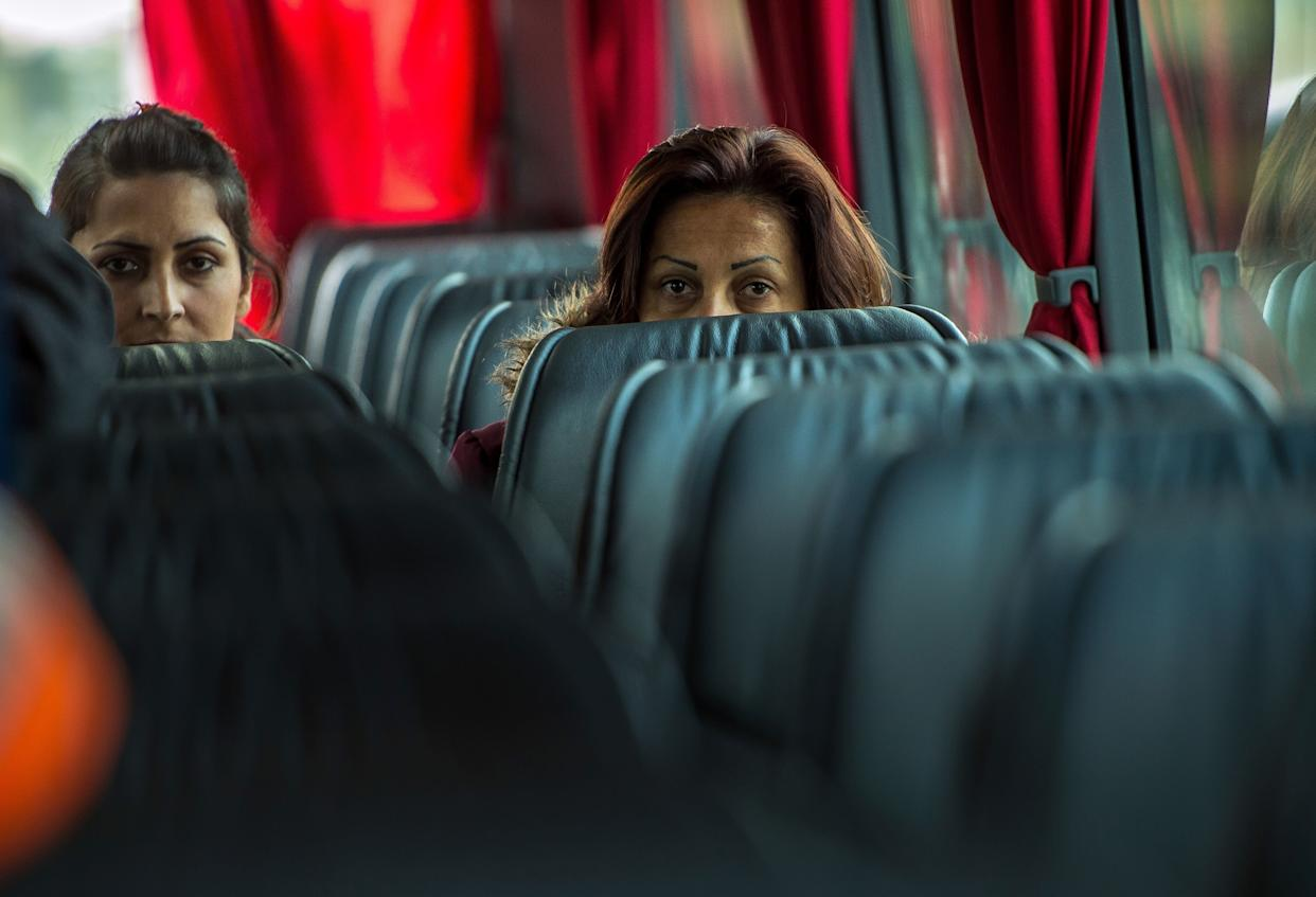 Kurdish Iraqi women leave aboard a bus the 'Jungle' migrant camp in Calais, northern France, on October 12, 2016, for a reception and guidance centre (CAO - Centre d'accueil et d'orientation).