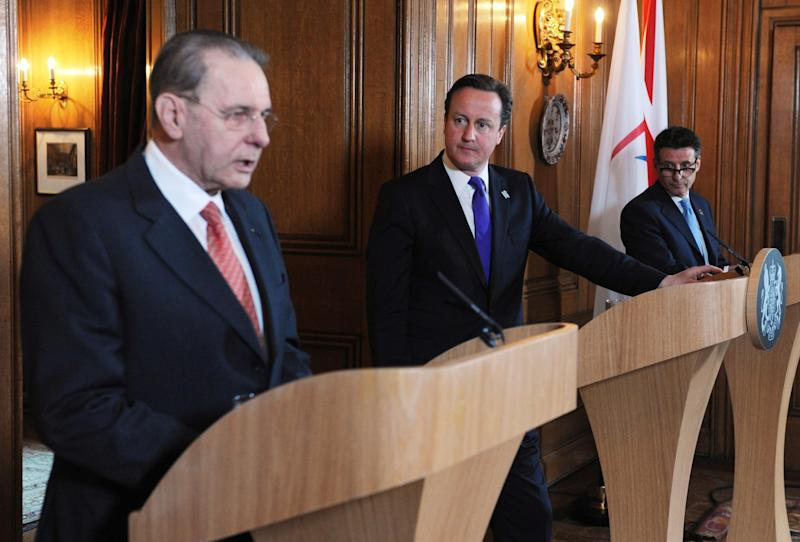 Britain's Prime Minister David Cameron, centre,  holds a news conference with IOC President Jacques Rogge, left, and Sebastian Coe Chairman of the London Organising Committee for the Olympic Games, at 10 Downing Street in London Wednesday March 28, 2012. Cameron said  his country has tough work ahead to make sure ordinary people benefit from the legacy of the London Olympics. Cameron was meeting Wednesday with International Olympic Committee President Jacques Rogge and officials, amid the final inspection visit before the games by the IOC coordination commission. The Olympics open in London on July 27. (AP Photo/Stefan Rousseau/Pool)