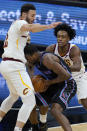 Sacramento Kings forward Harrison Barnes, middle, is defended by Cleveland Cavaliers forward Larry Nance Jr., left, and guard Collin Sexton during the first half of an NBA basketball game in Sacramento, Calif., Saturday, March 27, 2021. (AP Photo/Jeff Chiu)